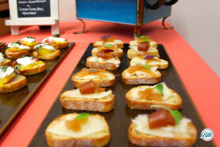 Tapas style crostini bite with manchego cheese and micro green garnish on cutting board display