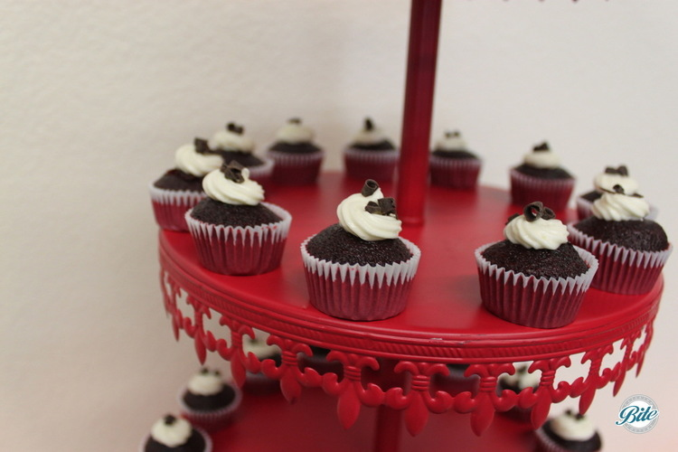 Mini chocolate cupcakes with buttercream frosting on red tiered display