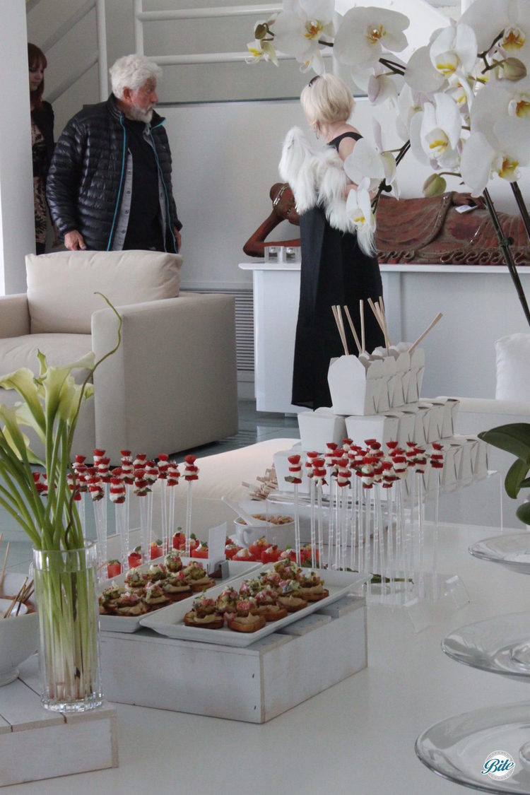 Crostini, individually boxed noodles, and caprese skewers on a white display