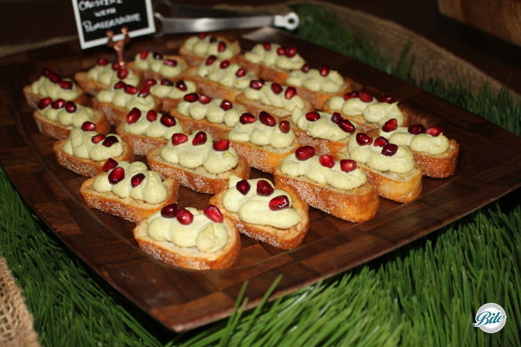Creamy edamame hummus served on crostini with pomegranate jewels on rustic display with faux grass and burlap