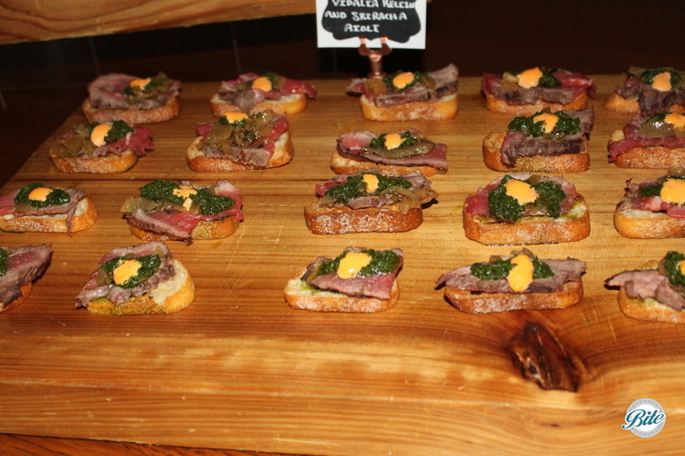 Grilled flank steak crostini with sriracha aioli on a wooden platter