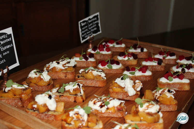 Roasted beet and goat cheese crostini on a wooden display.