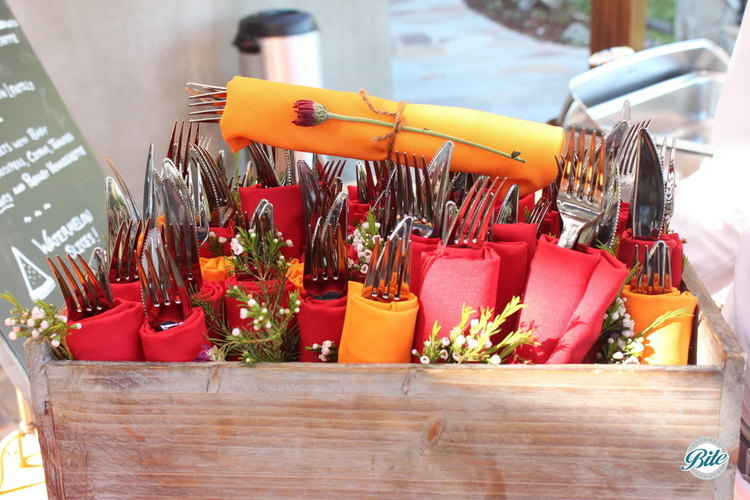Utensil roll ups with red napkins and wildflowers