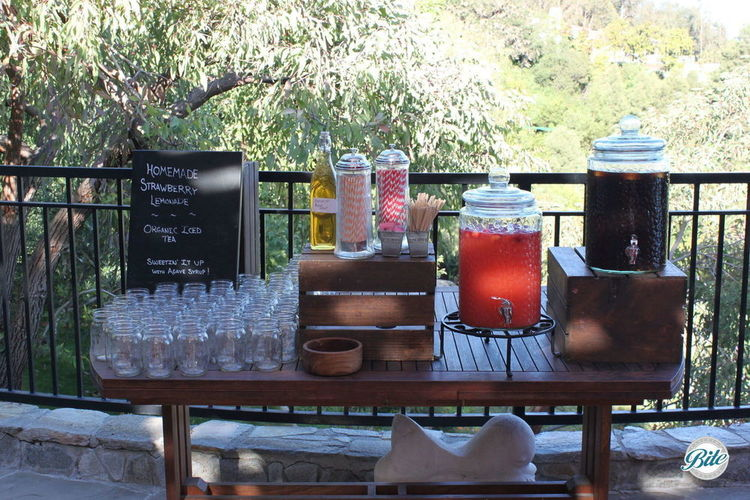 Rustic BBQ beverage station with homemade lemonade in beverage dispensers on wooden crates with chalkboard signage