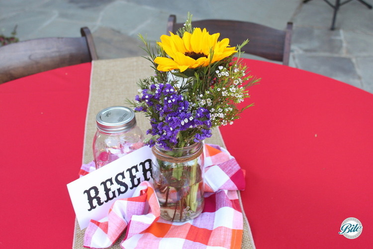 Picnic style outdoor party decor. Centerpiece with sunflowers, burlap, and mason jars