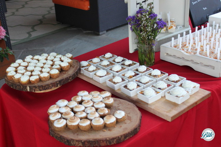 S'mores bites on wood log displays and mini peach cobblers on individual square trays