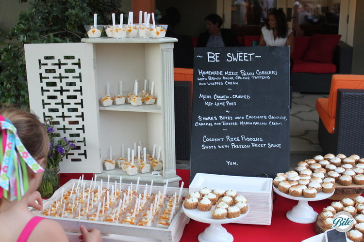 Dessert display for BBQ themed backyard event. Includes mini peach cobbler, mini cashew crusted key lime  pies, s'mores bites, and coconut rice pudding shots. Displayed with a chalkboard sign.
