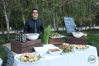 Contemporary market salad display with server ready to meet guests. Outdoor event with lanterns, grass, wood and porcelain display pieces