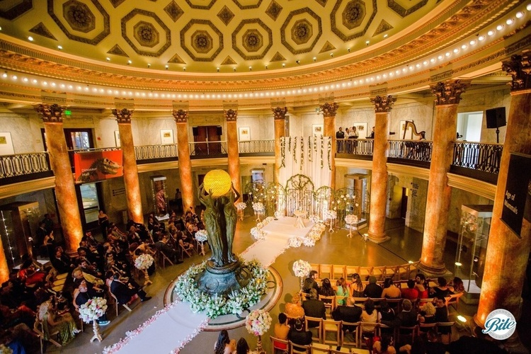Rotunda at NHM set up for wedding with chairs and altar. Harp playing in the upper level.