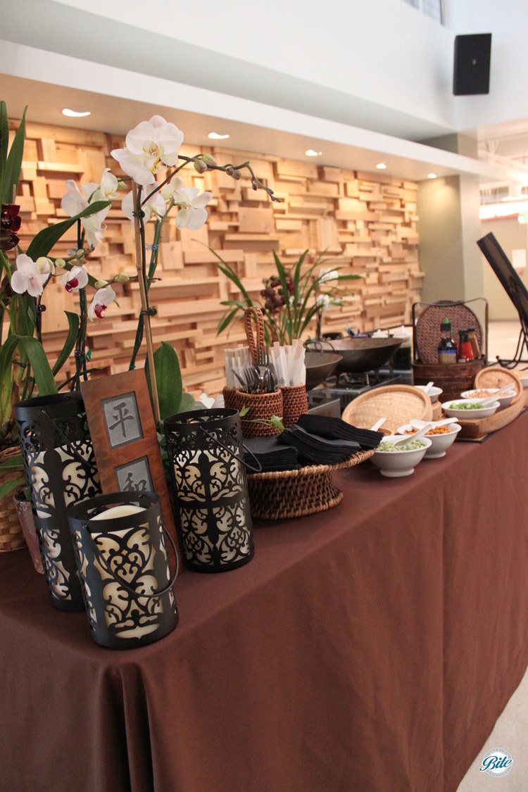 Wok station with noodles and accompaniments displayed with orchids and asian inspired decor
