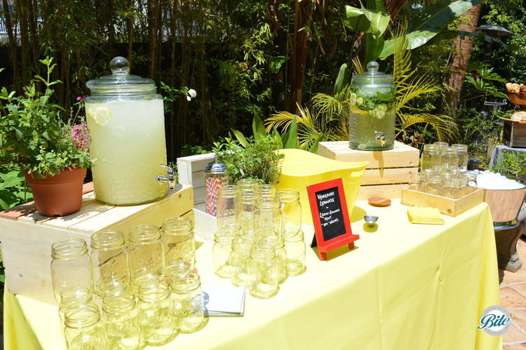 Outdoor beverage station with cucumber, mint and lemon infused water along with fresh lemonade on summer inspired display with mason jars, straws, fresh flowers and yellow table linen