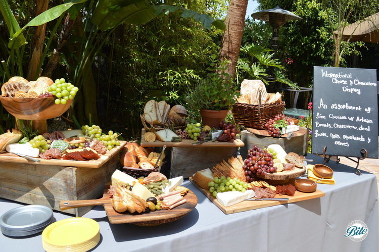 Beautiful outdoor cheese and charcuterie display including: artisan bread, an international cheese assortment, soppressata, prosciutto, Italian salami, pate, pickled accompaniments, and grapes