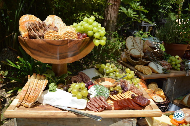 Beautiful cheese and charcuterie display on wood risers and bowls