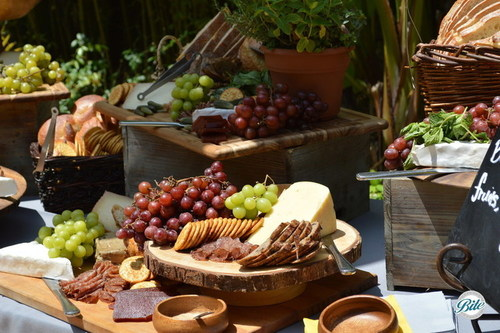 Cheese on wood riser with crackers, grapes, charcuterie