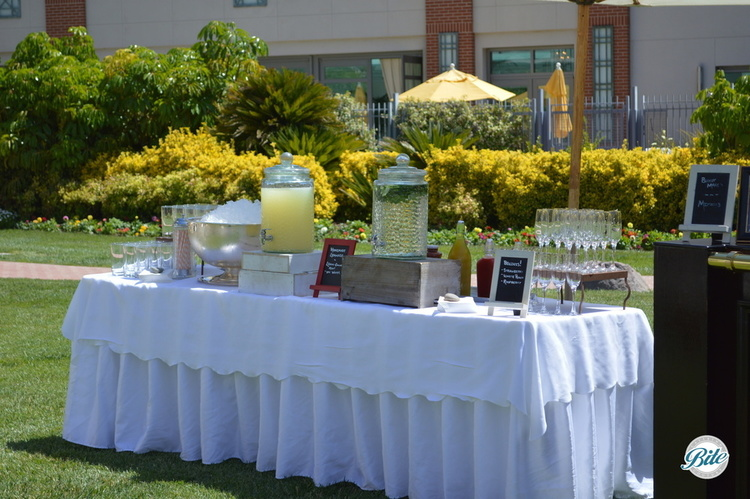 Beverage station with spa water, fresh lemonade, and champagne on outdoor set up for guests