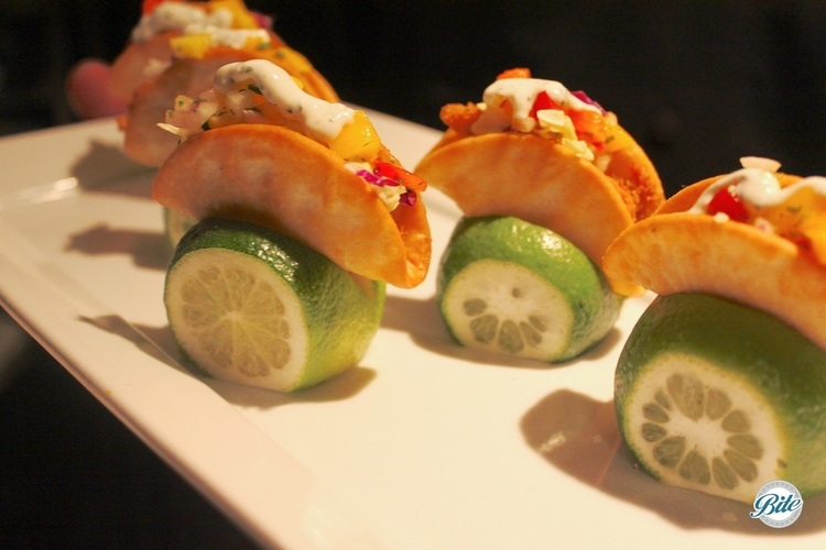 Mini Fish Tacos with tropical salsa and crema presented in a lime wedge