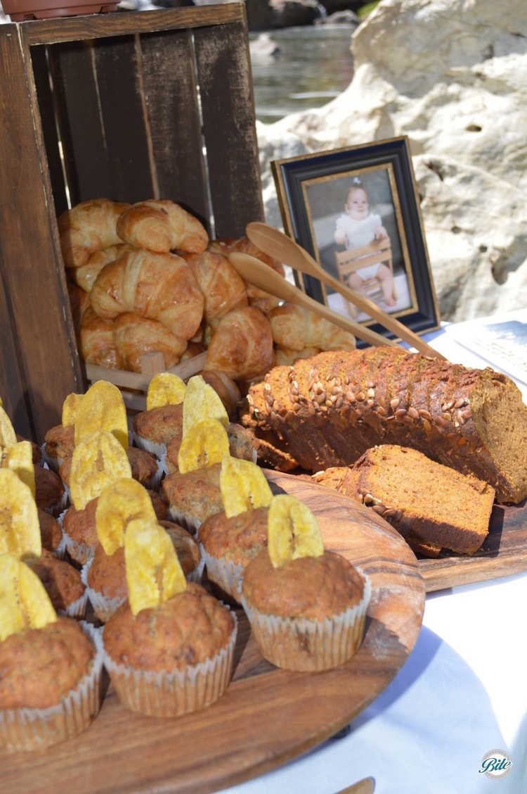 Muffins, croissants, and breakfast bread laid out on rustic brunch display for bridal shower