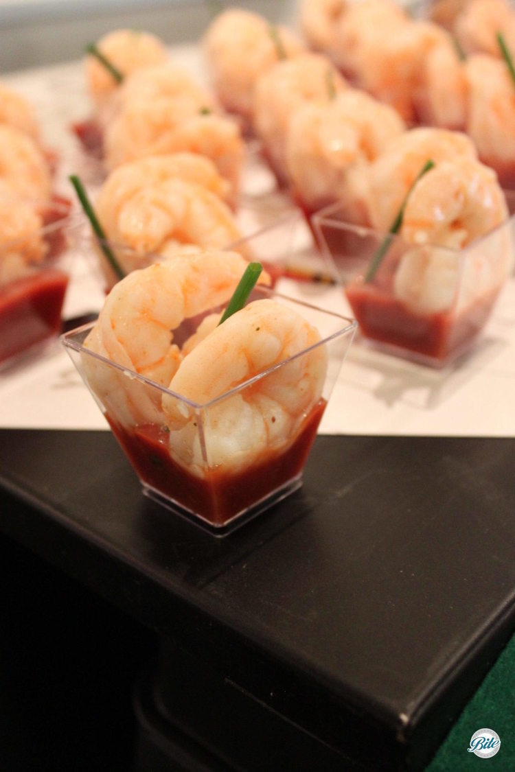 Shrimp Cocktail in individual shot glasses with cocktail sauce and herb garnish