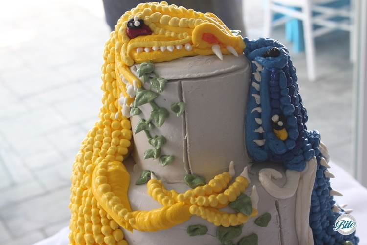 Closeup of wedding cake topper with blue and yellow dragons